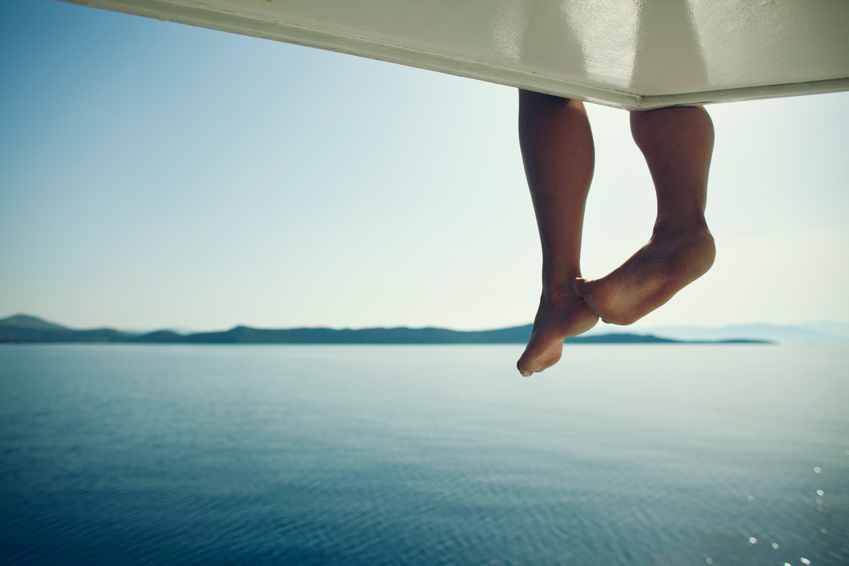 the ocean with someone sitting on a boot and their feet dangling down above the water