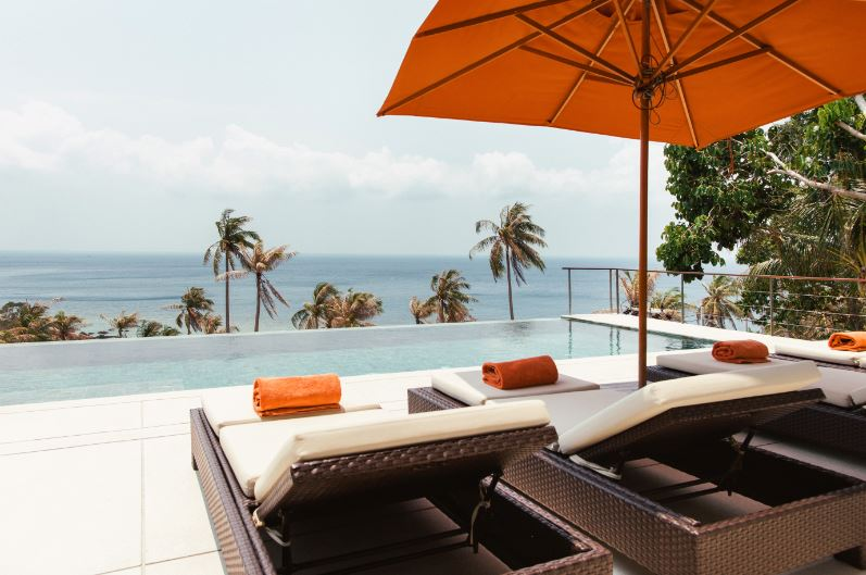 some lounge chairs and umbrella in front a pool with the ocean behind it