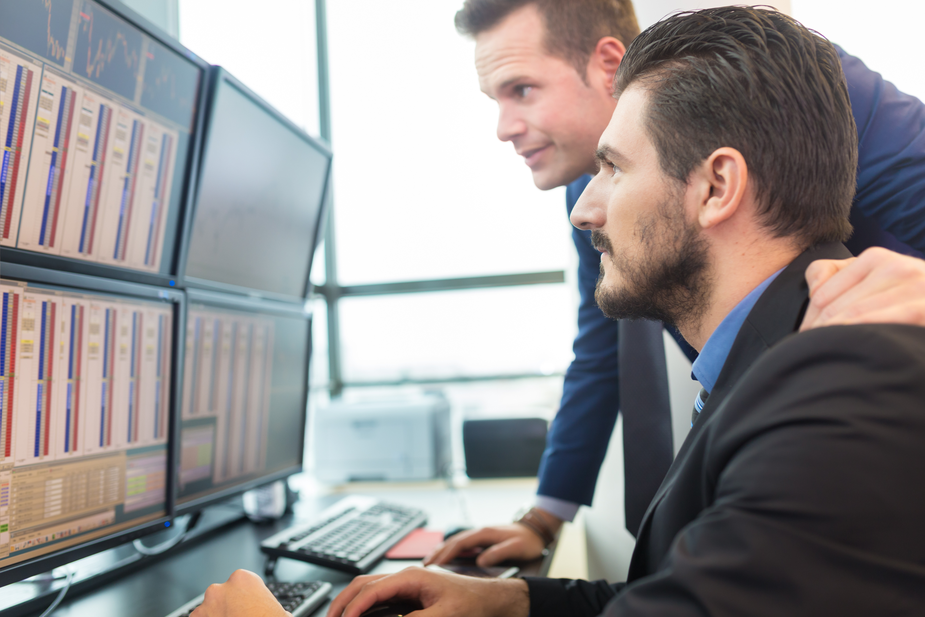 two men looking at computer screens of investments