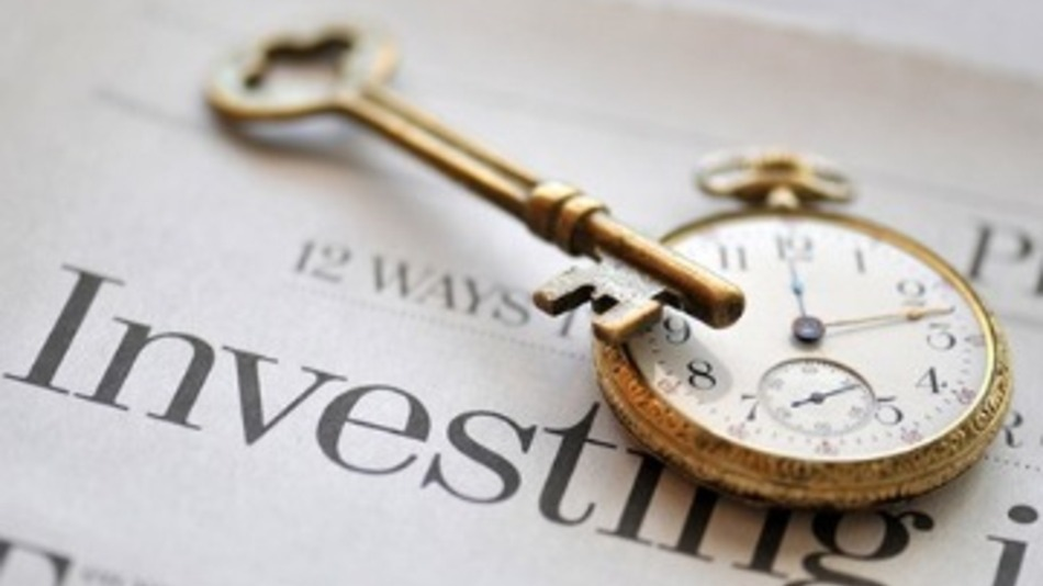newspaper that says investing with a pocket watch and key on top