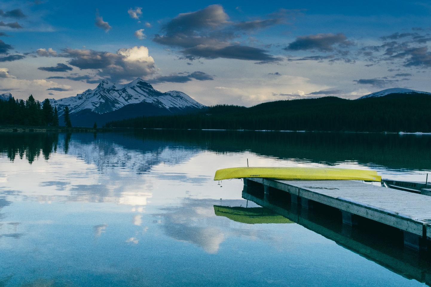Scenic view of mountains and lake with canoe on dock